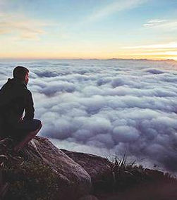 man crouching on mountain top looking over the clouds