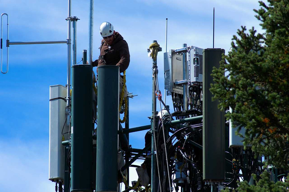 Worker doing maintenance work on mobile signal mast