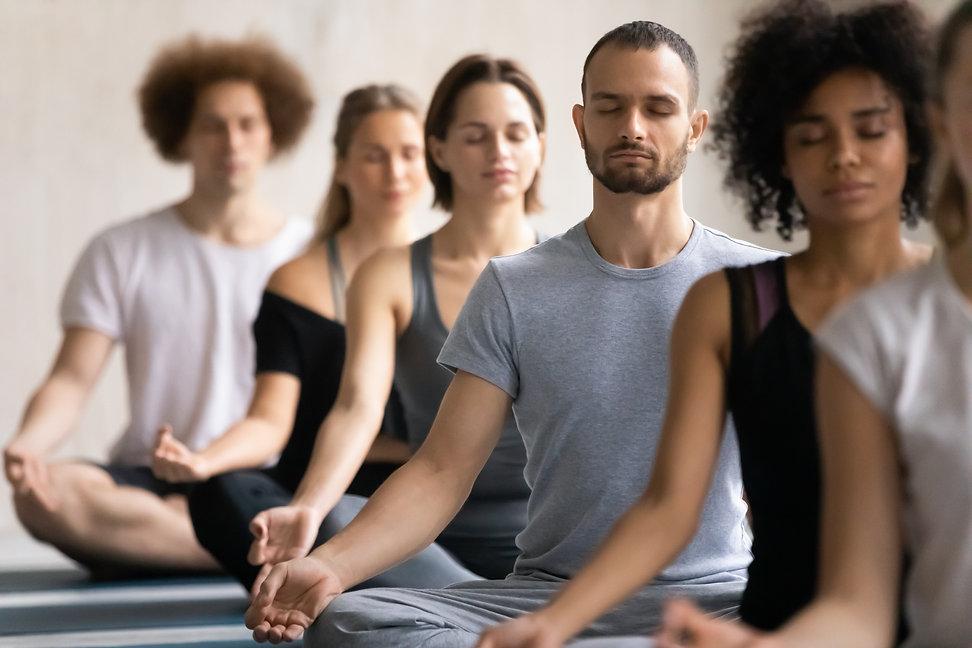Group of diverse people meditating toget