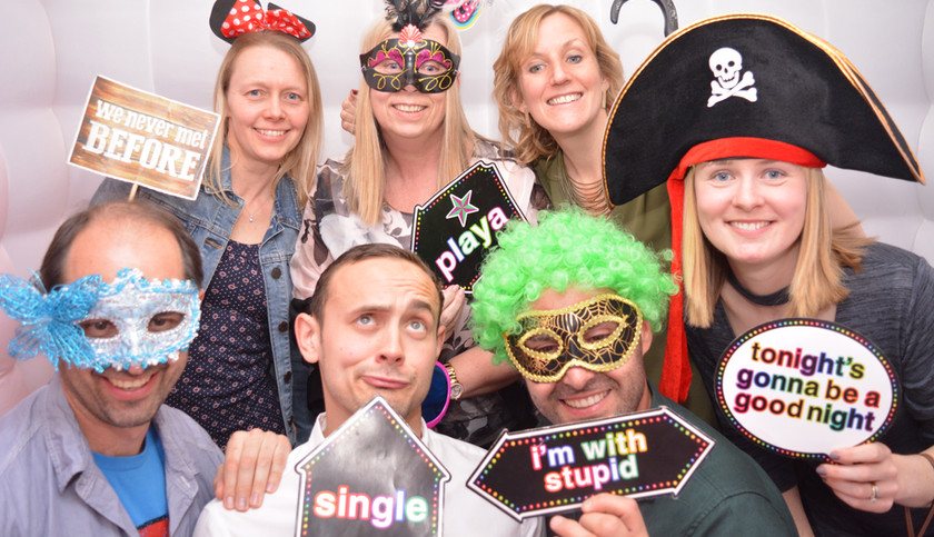 7 People wearing props enjoying the photo booth at a birthday party