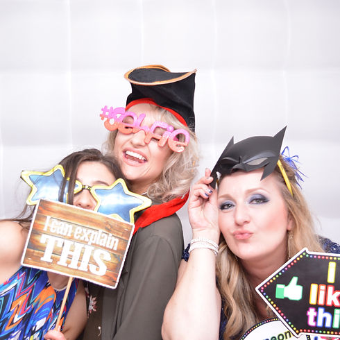 3 Girls enoying the props inthe photo booth at thier prom