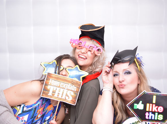 3 Girls wearig props enjoying the photo booth at their prom
