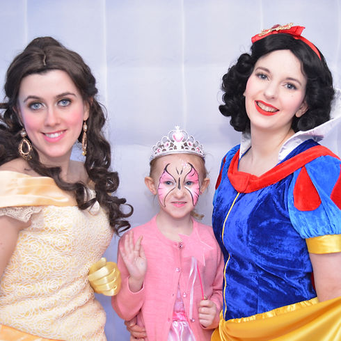 Princess Belle and Snow White posing with little girl in the photo booth at a childrens birthday party