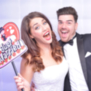 Newly married couple having fun in the photo booth at thier wedding