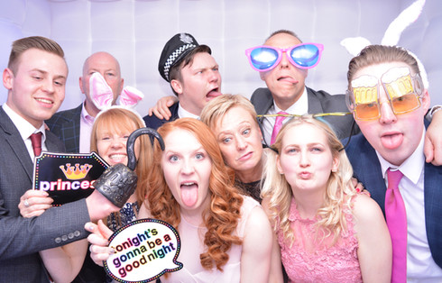 7 People wearing props and having fun in the photo booth at a corporate event