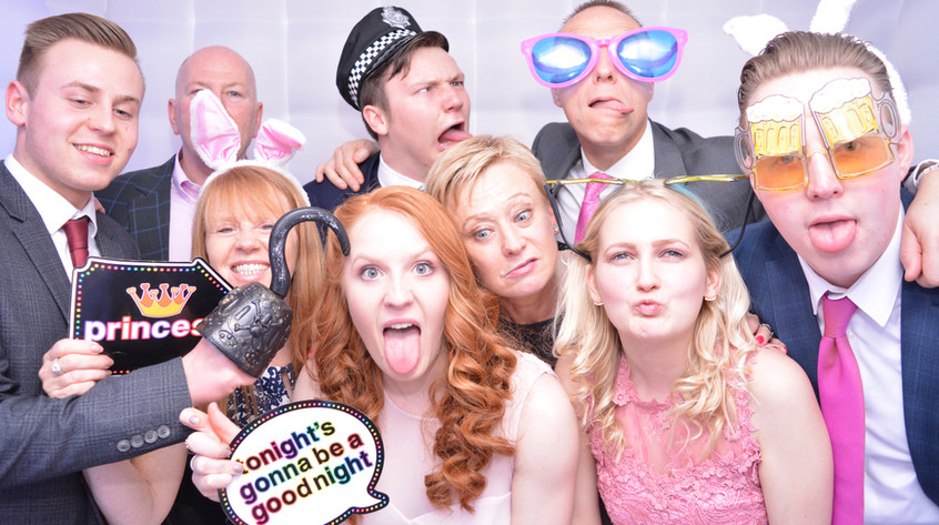 9 People wearing props enjoying th photo booth at thier Corporate party