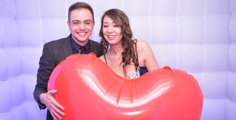 Newly engaged couple with giant love heart enjoying the photo booth at thier engagement party
