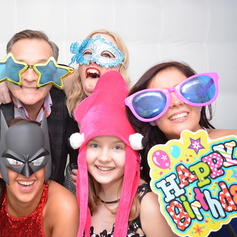 5 People wearing funny props enjoying the photo booth at a birtday party
