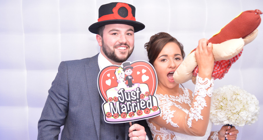 Bride and Groom wearing props enjoying the photo booth at thier wedding