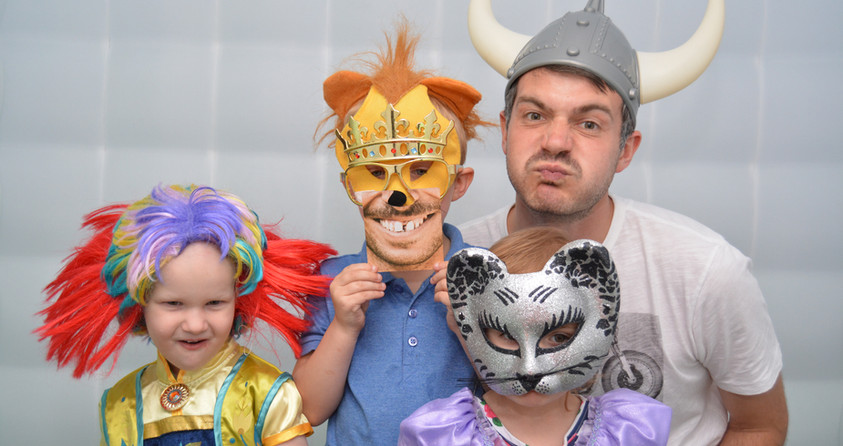 1 Man and 3 Children wearing props enjoying the photo booth at a childrens birthday party