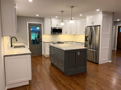 side view of kitchen remodel with white cabinets and grey kitchen island