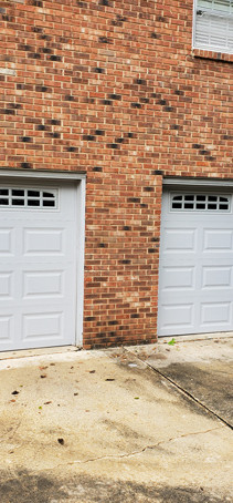 Two white garage doors with small windows