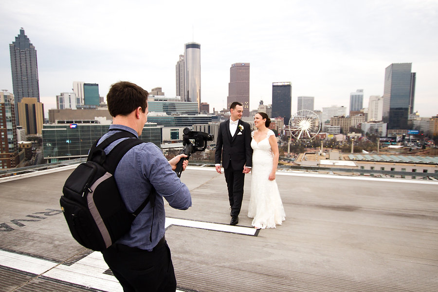 wedding videographer in Atlanta filming bride and groom on rooftop with ferris wheel in background