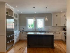front view of kitchen remodeling project with white cabinets and grey kitchen island