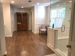 bathroom renovation project with wood floors and glass shower and custom storage