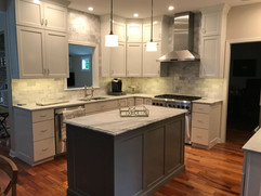 grey kitchen remodel with subway tile and large dark grey kitchen island