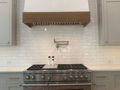 front view of kitchen remodel with stove and range hood