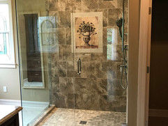 bathroom remodel with tiled shower and glass surround