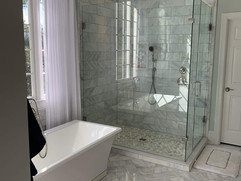 bathroom renovation with tiled floor and bathtub and glass shower