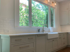 kitchen remodel with grey cabinetry and large window over sink