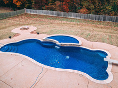 fiberglass pool with diving board and hot tub built by Butler Pool and Spa