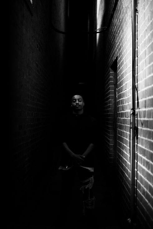 Rapper NiccoFeem standing in dark alley