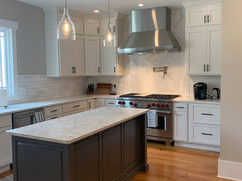 side view of kitchen remodel with grey kitchen island and white cabinets
