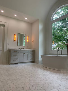 bathroom renovation with tub under window and grey cabinets