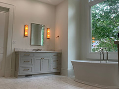 grey bathroom renovation with tub under large window and tiled floors