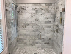 bathroom remodeling project with floor to ceiling grey tiled shower and inset shelving