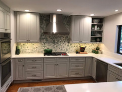 kitchen remodel project grey cabinets and white counters and built in stove top with range hood