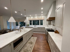 large kitchen renovation with double sinks and oven with range hood white countertops and kitchen island with built in sink and microwave