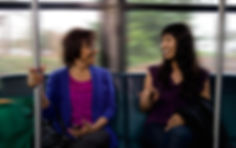 two woman talking on a bus