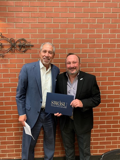 SWOSU Foundation, Inc. Board of Trustees Chairman George Cohlmia (left) offers best wishes to outgoing SWOSU President Dr. Randy L. Beutler during a recent trustees meeting held at SWOSU's Weatherford location. Photo provided.