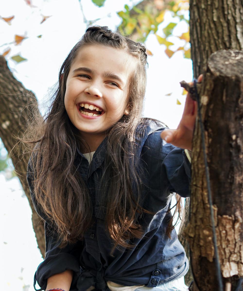 Menina rindo em uma árvore