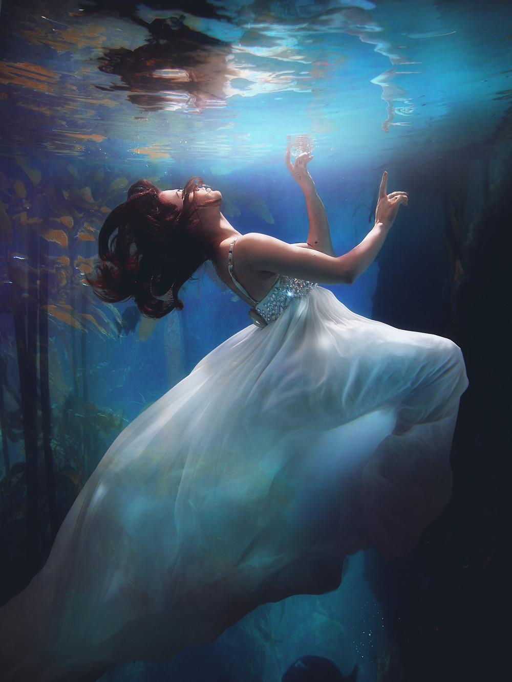 Mulher dentro do mar subindo para a superfície