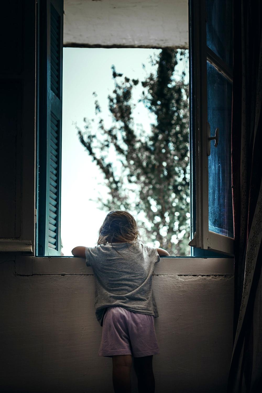 Menina olhando dentro de uma casa olhando através da janela