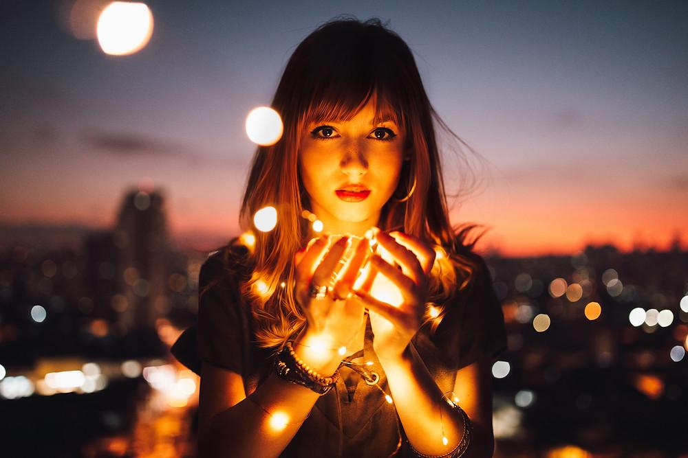 Mulher segurando algumas pequenas luzes na mão