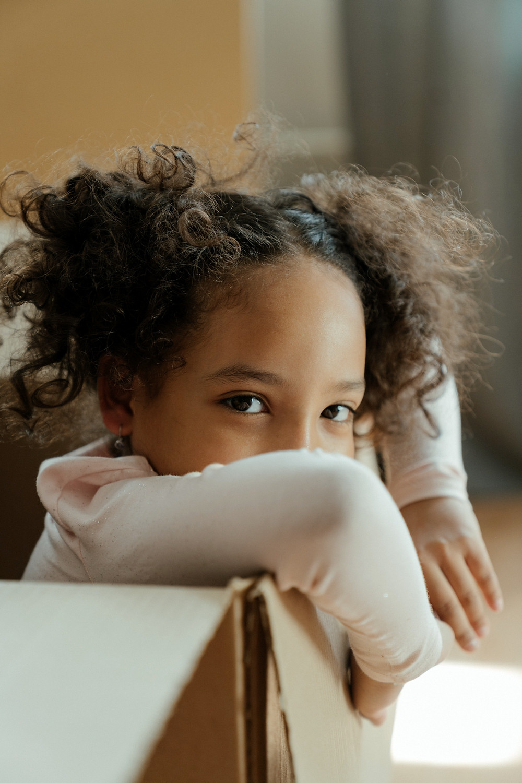 Criança brincando dentro de uma caixa de papelão