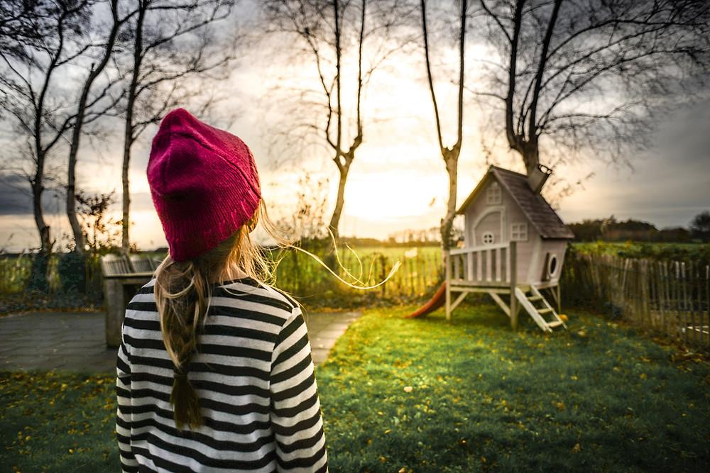 Menina olhando uma casa pequena