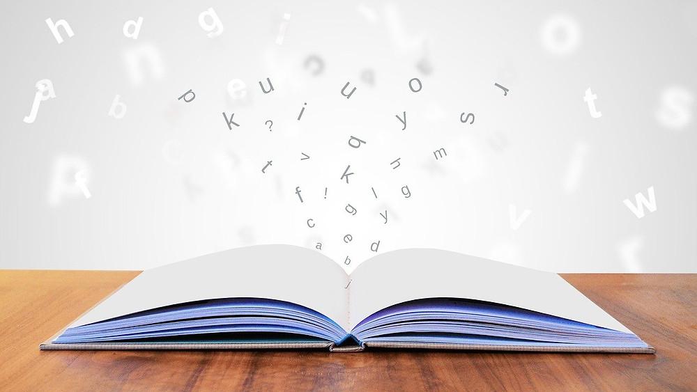 Livro aberto com letras saindo e voando