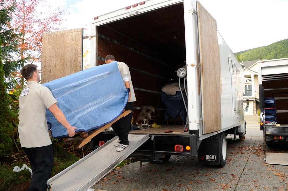 movers moving furniture into a truck