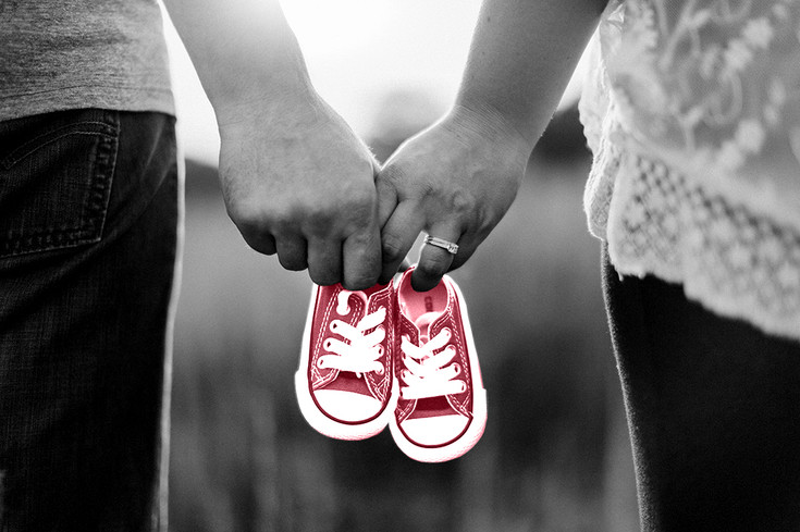 couple holding hands with small baby shoes converse engagement ring pregnancy announcement black and white with colour