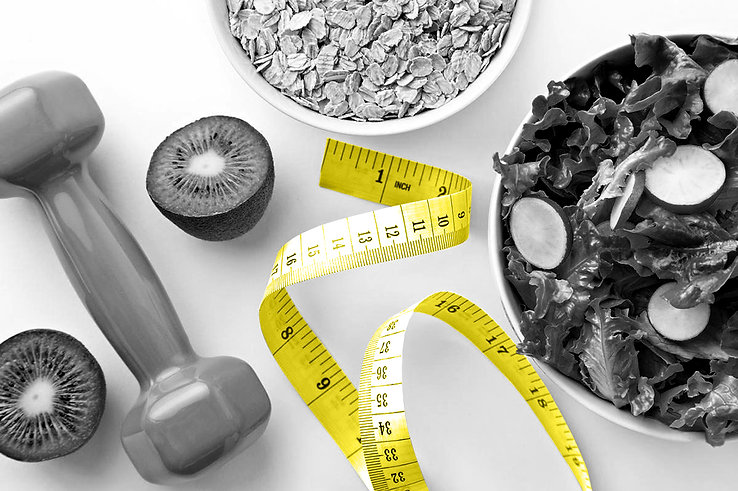 tape measure for body measurement in weight loss on table with salad, oats, fruit and dumbell weight black and white with colour yellow