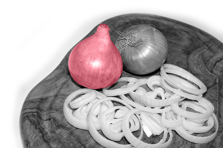 onions on a chopping board cut into rings crying pink accent colour black and white with colour