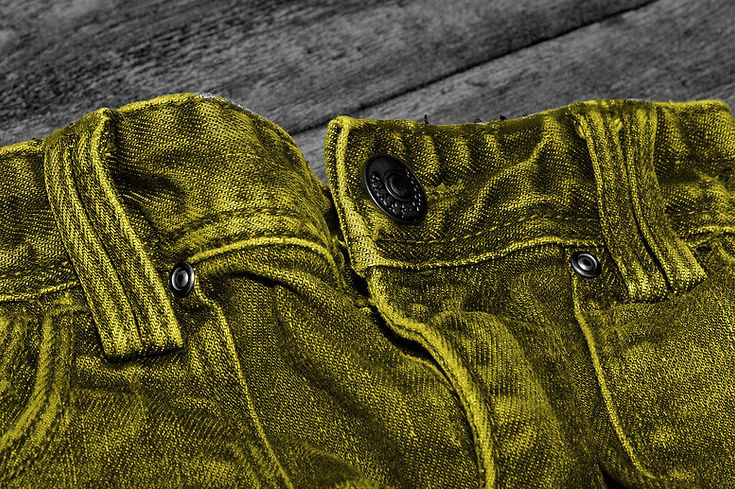 jeans lying out on wooden table crotch button and flies yellow denim black and white with colour