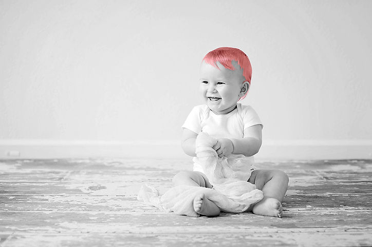 baby sitting laughing and smiling on wooden floor with a blanket black and white with colour pink hair