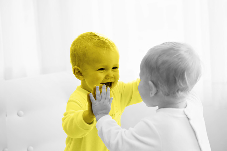 baby looking in the mirror at itself laughing and smiling at reflection in baby grow yellow black and white with colour