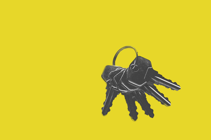keys lying out on yellow background held together with a keyring black and white with colour