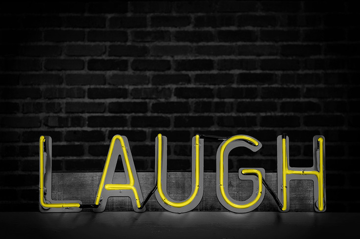 the word laugh written in neon lights against a rustic brick wall yelow lights black and white with colour
